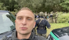 Robert Bąkiewicz na granicy polsko-białoruskiej. W tle uchodźcy
