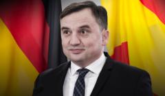 Zbigniew Ziobro na tle flag: niemieckiej i hiszpańskiej