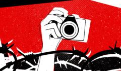 Wyprostowana ręka trzymająca aparat fotograficzny, na dole grafiki są druty kolczaste