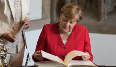 kanclerz Angela Merkel przegląda księgę gości w kolońskim ratuszu