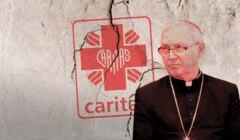 Biskup płocki Piotr Libera na tle popękanego logo Caritas.