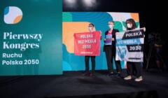 aktywiści Greenpeace trzymają tablicę z postulatami odejścia od węgla do 2030 roku na scenie kongresu ruchu Polska 2050