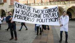 """Osoby trzymające transparent z napisem """"Operuję twoje dziecko w 30 godzinie dyżuru. Podziękuj politykom"""