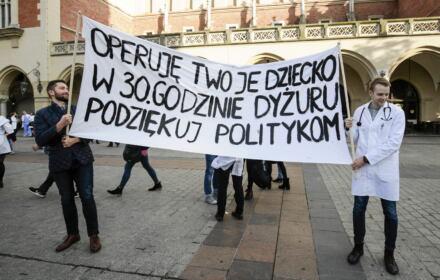 """Osoby trzymające transparent z napisem """"Operuję twoje dziecko w 30 godzinie dyżuru. Podziękuj politykom"""" podczas manifestacji solidarnościowej ze strajkującymi rezydentami, Rynek Główny w Krakowie, 2017 rok"""