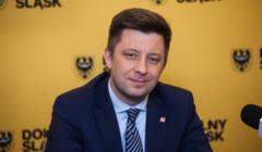 Michał Dworczyk wdzięczy się do aparatu na tle planszy reklamującej Dolny Śląsk