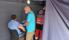 Katowice. Punkt szczepień przy straży pożarnej, strażak szczepi mężczyznę.