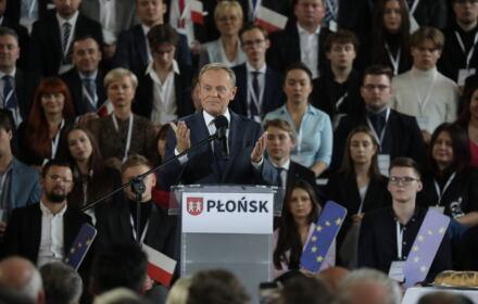Donald Tusk przemawia na konwencji PO w Płocku, trzyma przed sobą rozłożone dłonie