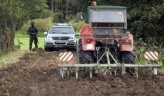 Usnarz Górny. Traktor zaorywuje drogę do granicy, na drugim planie policyjny radiowóz