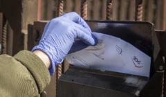 dłoń w rękawiczce wrzuca do skrzynki rachunek za energię elektryczną