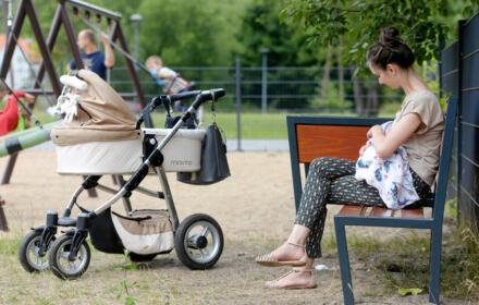 Matka z dzieckiem na ręku na placu zabaw