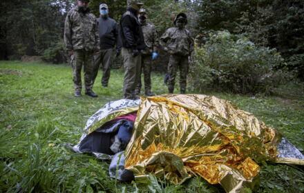 Uchodźcy na granicy polsko-białoruskiej chroniący się pod folią termoizolacyjną