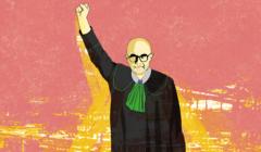 Adwokat Radosław Baszuk w todze adwokackiej, z uniesioną triumfalnie w górę pięścią