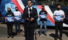 premier Mateusz Morawiecki na konferencji prasowej. W tle autokar reklamujący Polski Ład