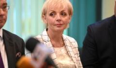 Anna Kwiecień, blond włosy, krótko obcięte, w jasnej garsonce w dużą kratę,