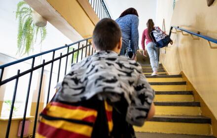 Szkoła w Bezwoli ma być zlikwidowana. Na zdjęciu chłopczyk wczhodzi po schodach, przed nim kobieta z zasłoniętą głową prowadzi córkę