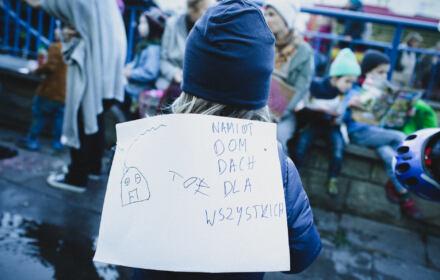 Dziecki z rysunkiem domu dla uchodźców przed siedziba straży granicznej w Warszawie