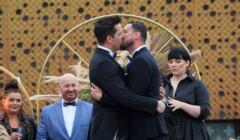 Maciej Socha i Mateusz Wartęga całują się podczas uroczystości weselnej